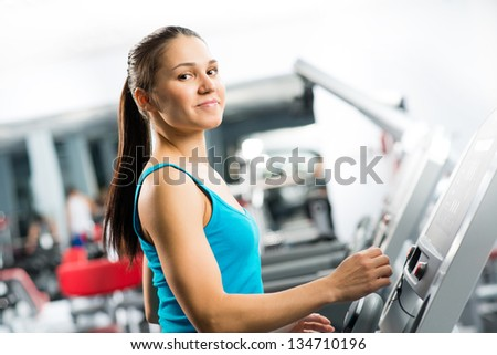 attractive young woman runs on a treadmill, is engaged in fitness sport club - stock photo