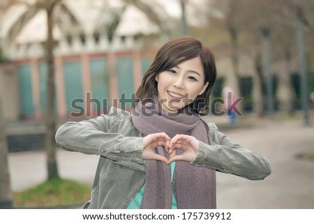 Attractive young woman showing a love shape gesture in the park, Taipei, Taiwan.