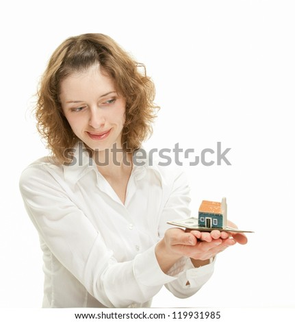 Attractive young woman showing dollar banknotes and small house; concept of investment in real estate