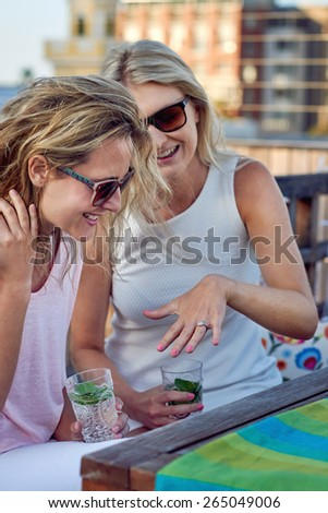 attractive young woman showing friend her engagement ring outdoor on the rooftop terrace - stock photo