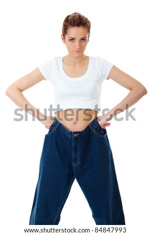 Attractive young woman shows her old huge jeans, isolated on white - stock photo