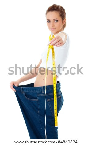 Attractive young woman shows her old huge jeans, successful dieting concept shoot over white background, foreground focus