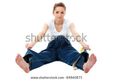 Attractive young woman shows her old huge jeans, successful dieting concept shoot over white background - stock photo