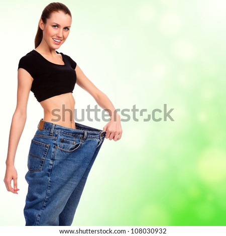 attractive young woman shows her old huge pair of jeans, weight loss concept, green blurred background - stock photo