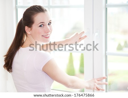 Attractive young woman shuts window - stock photo