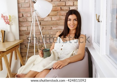 Attractive young woman sitting at cosy home, smiling, drinking tea.