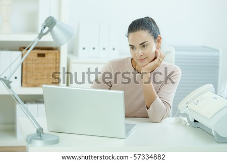 Attractive young woman sitting at desk, looking at laptop computer screen, thinking. - stock photo