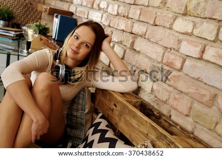Attractive young woman sitting at home, relaxing. - stock photo