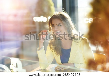 Attractive young woman sitting at the table in cafe - stock photo