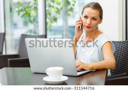 Attractive young woman sitting in a cafe with a laptop and talking on the cell phone
