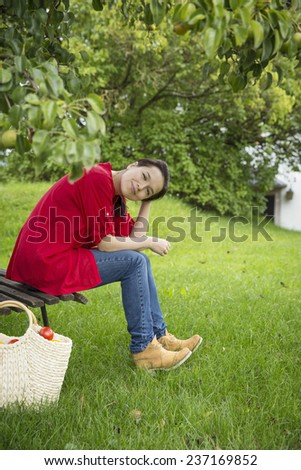 attractive young woman sitting on a wooden bench under a pear tree and smiling towards a camera - stock photo