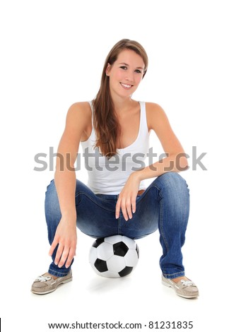 Attractive young woman sitting on soccer ball. All on white background.