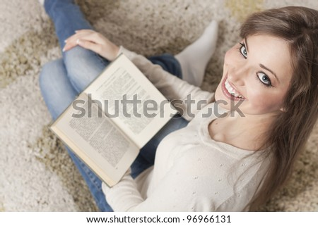 Attractive young woman sitting on the floor at home and reading a book - stock photo