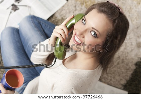 Attractive young woman sitting on the floor at home and speaks by phone