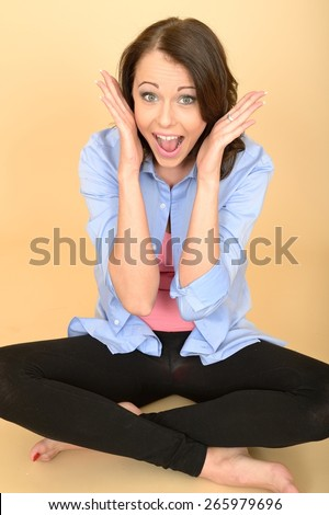 Attractive Young Woman Sitting on the Floor Wearing a Blue Shirt and Black Leggings Pulling Silly Facial Expressions and Acting the Fool
