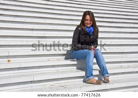 Attractive young woman sitting on the marble steps and smiles in the sunlight. - stock photo