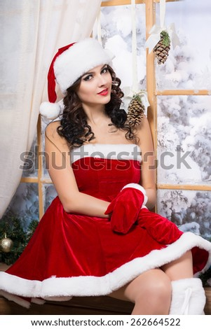 Attractive young woman sitting on the windowsill wearing like Santa`s helper - stock photo