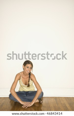 Attractive young woman sitting with her legs crossed on the floor. She is smiling towards the camera. Vertical shot. - stock photo