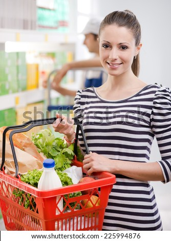 Attractive young woman smiling and holding a shopping basket at store. - stock photo