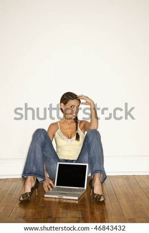 Attractive young woman smiling and sitting on the floor with a laptop between her legs. Vertical shot. - stock photo