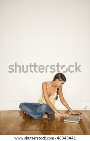 Attractive young woman smiling and sitting on the floor with a laptop. Vertical shot. - stock photo