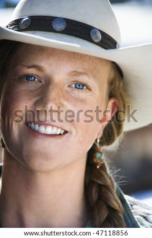 Attractive young woman smiling and wearing a cowboy hat. Vertical shot. - stock photo