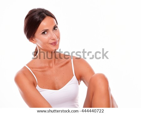 Attractive young woman smiling happily while looking at camera with her knee up while wearing a white tank top and hair tied back, isolated