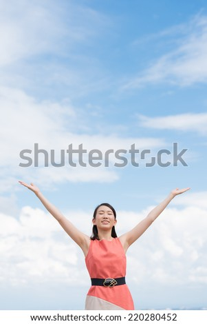 attractive young woman spreading arms on sky background.