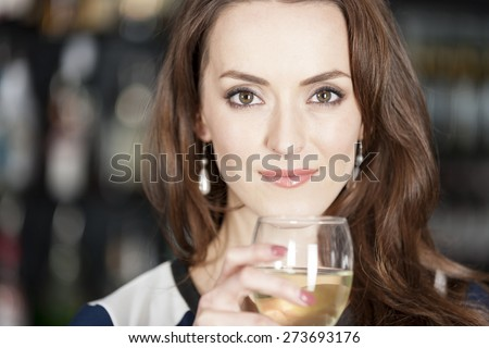 Attractive young woman standing in a wine bar with a glass of wine - stock photo