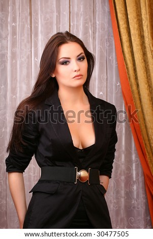 attractive young woman standing in hall wearing suit - stock photo