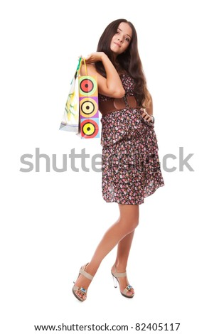 attractive young woman standing with bags shopping on shoulder over white background - stock photo