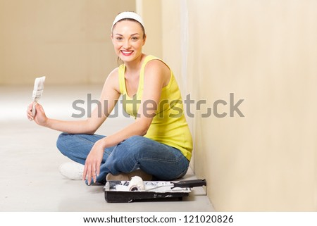 attractive young woman taking a break while painting her new home - stock photo