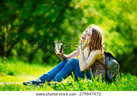 Attractive young woman talking by phone and holding cup of coffee outdoors. Sitting at the grass in park. Casual outfit, backpack.  - stock photo