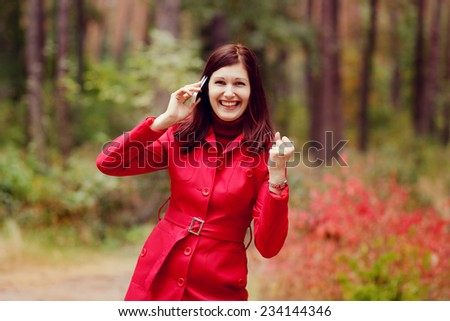 """Attractive young woman talking on the phone in nature. Joyful emotions of good news, the gesture """"yes"""" - stock photo"""