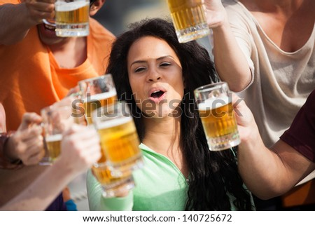 Attractive young woman toasting with a delicious Pale Ale  Beer