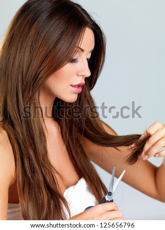 Attractive young woman trimming the ends of her long brunette hair with a pair of scissors to remove split ends - stock photo