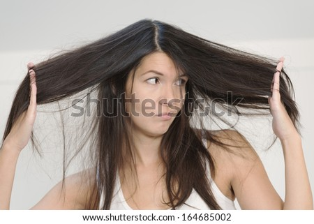 Attractive young woman unhappy with the condition her long hair standing grimacing at the camera with her hands entwined in her tresses holding the hair out on either side of her face
