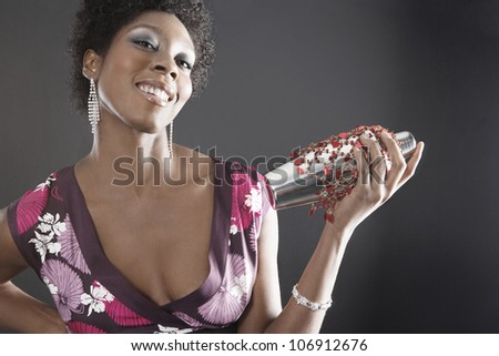Attractive young woman using a cocktail shaker to mix drinks, smiling. - stock photo