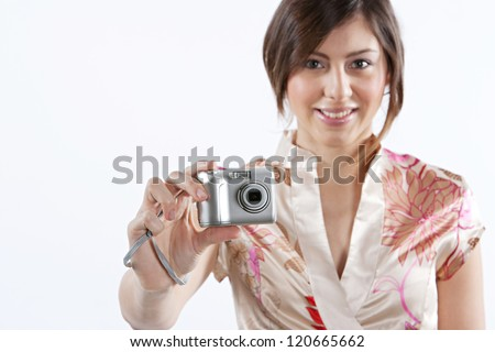 Attractive young woman using a digital photographic camera while standing isolated against a plain white background, smiling at the camera. - stock photo