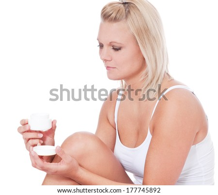 Attractive young woman using body lotion - stock photo