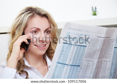 Attractive young woman using her phone while reading the newspaper - stock photo