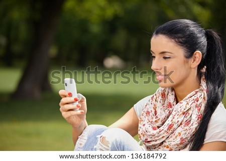 Attractive young woman using mobile, sitting in park, smiling. - stock photo