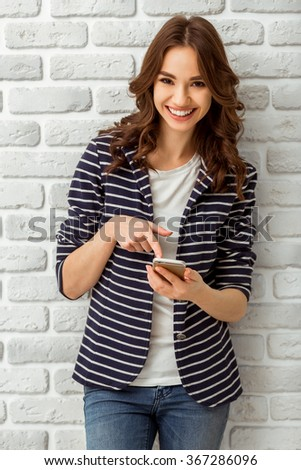 Attractive young woman using the phone with a smile, standing on the brick wall background - stock photo
