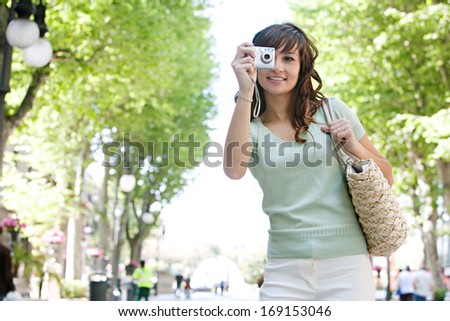 Attractive young woman visitor using a digital photographic camera to take pictures of a destination city street avenue with green trees, while on a summer holiday trip during a sunny day. - stock photo
