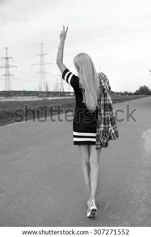 Attractive young woman walking down the road white black. Vertical full length image. - stock photo