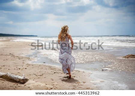 Attractive young woman walking on the beach. Travel and Vacation.Soft focus
