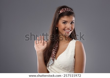 Attractive young woman waving, smiling happy. - stock photo
