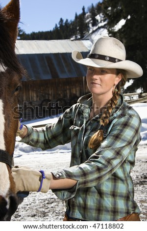 Attractive young woman wearing a cowboy hat and petting a horse. Vertical shot. - stock photo