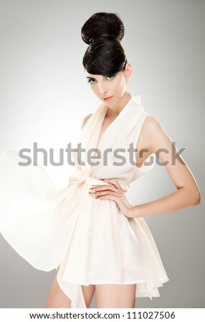 Attractive young woman wearing a wind-blown see-through dress looking at the camera. She has a hand on the waist and a provocative look in her eyes. - stock photo