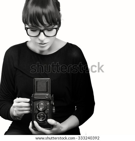 Attractive Young Woman Wearing Black Clothes and Glasses Capturing Photo Using Vintage Camera. Monochrome Portrait Isolated on White Background with Copy Space for Text - stock photo